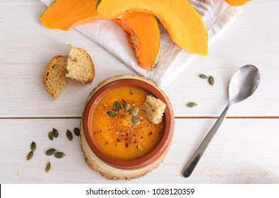 Top view of  pumpkin soup with pumpkin seeds and spice, served in ceramic bowl and fresh toasts on wooden table. Easy healthy plate for dinner. Vegetarian diet and lifestyle.