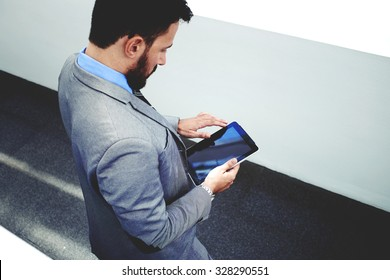 Top view of a purposeful intelligent lawyer man holding touch pad with copy space screen for your promotional content, young male skilled manager in luxury suit using digital tablet in modern office