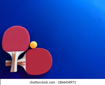 Top view of racket and table tennis ball on blue black ground