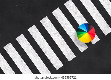 Top view of a rainbow umbrella on a pedestrian crosswalk
