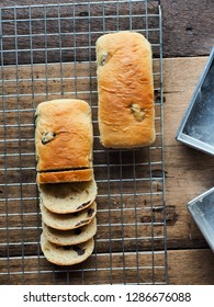 Top view of raisin bread loaf both whole piece and slices on wood table with baking tin mold.