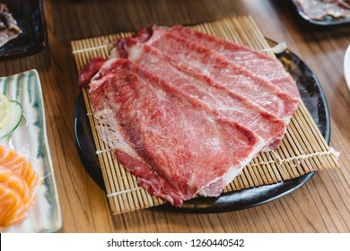 Top view of Rare slices Wagyu A5 beef on bamboo mat with black plate for boiling in Shabu soup hot pot.