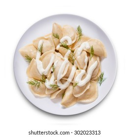 A top view of ravioli with parsley on the plate. Isolated on white.