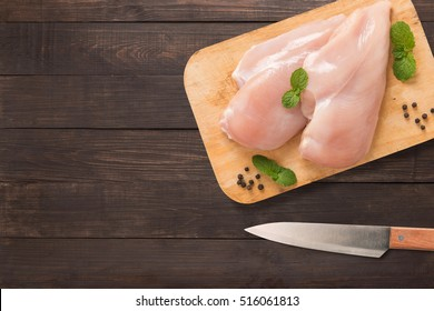 Top view raw chicken on cutting board and knife on wooden background. Copyspace for your text.