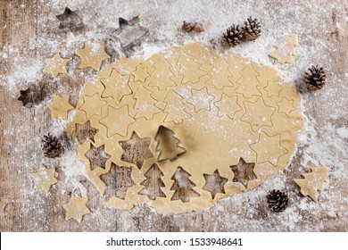 Top view of raw dough that is being cut to make cookies shaped like Christmas trees and stars on a floured wooden table and with pineapples. View from above. Recipes for children. Christmas desserts.
