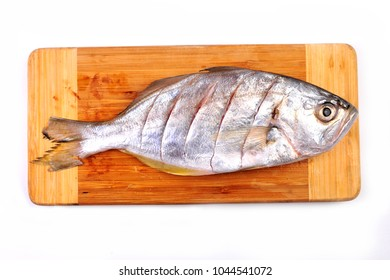 top view of raw fish - False trevally, Milkfish, Whitefish, Butterfishon - on chopping wooden board
