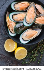 Top view of raw fresh kiwi mussels with lemon and thyme, vertical shot, close-up