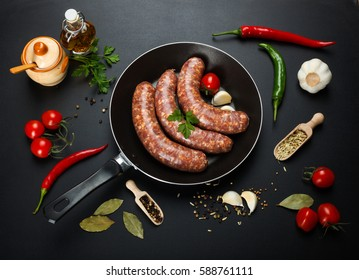 Top view of raw homemade pork sausages in frying pan on black background