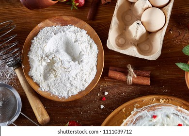 Top view raw ingredients for cooking strawberry pie or cake on wooden table, flat lay. Bakery background.