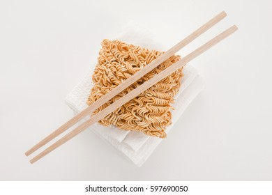 top view of raw instant noodle on white texture cloth with chopsticks on white background