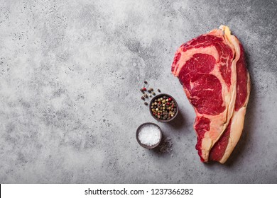 Top view of raw marbled juicy meat beef Rib eye steak ready for cooking, with seasonings, grey concrete rustic background, space for text