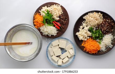 Vue de dessus matières premières prêtes à cuisiner des nouilles de riz faites maison, ingrédient végétalien comme champignon d'oreille de bois, carotte, pâte de riz, tofu haché sur fond blanc, plat populaire vietnamien