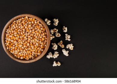 Top view raw popcorn in wooden bowl on black background and space for text