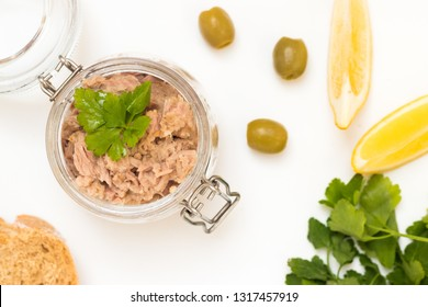 Top view raw tune in glass jar with lemon slices, olives and parsley. Healthy sea food with omega 3.