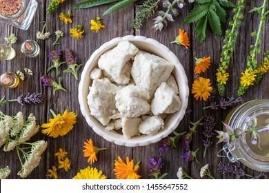 Top view of raw unrefined shea butter in a bowl with medicinal plants and essential oils - ingredients to prepare a homemade skin ointment