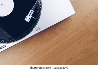 top view of a record player or turntable with a vinyl record on the wooden floor