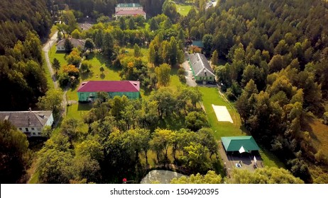 Top view of recreation center in forest with lake. Clip. Housing recreation in green forest near lake for country holiday. Forest recreation center for recreation near nature
