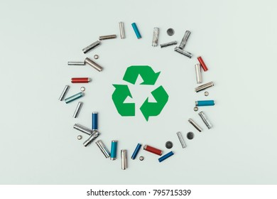 top view of recycle sign and various types of batteries in circle isolated on grey