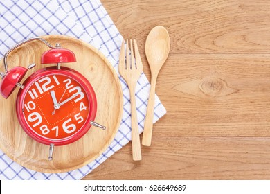 Top view red alarm clock in wooden dish, spoon and fork on wooden plank background. Time eating concept.