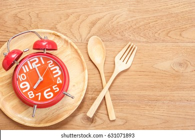 Top view red alarm clock in wooden dish, spoon and fork on wooden plank background. Time eating concept