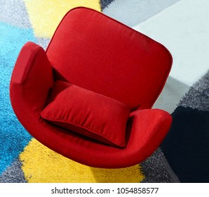 Top view of a red armchair on a colorful carpet