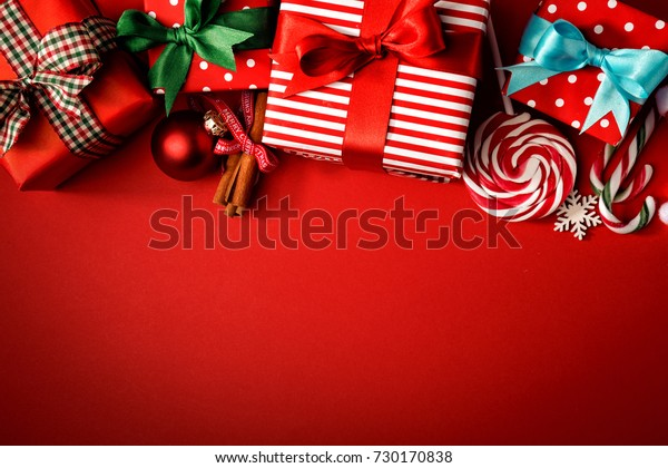 Top view of red background with composed giftboxes and sweets for Christmas holiday.