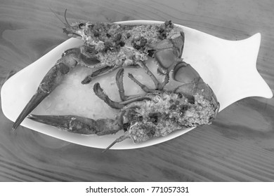 Top view of a red baked lobster with herbs on a white plate - black and white