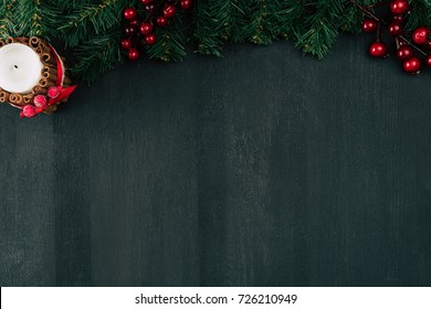 top view of red berries with branches and candle on black background