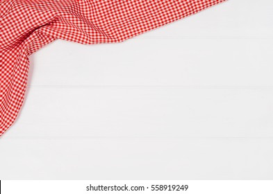 Top view of red checkered napkin or tablecloth on white wooden table with visible planks, texture and copy space for text.