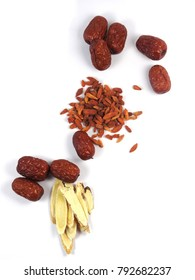 Top view of red dried jujube (called red date or Chinese date)  and goji berry (called wolfberry) and Astragalus slices isolated on white background.Those are traditional Chinese herbal medicine.
