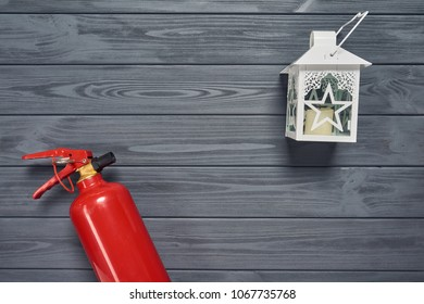 Top view of red fire extinguisher and candle lantern on wooden planks