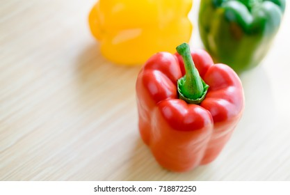 Top view of Red Green Yellow bell pepper background on wooden table.Paprika is a cultivar of the species Capsicum annuum paprika yield different colors.