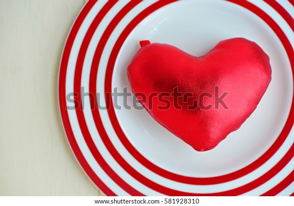 Top view of red heart on colorful plate, with wooden background. (Concept about love and relationship)