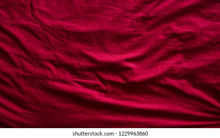 Top view of a red messy bedding sheet after night sleep.