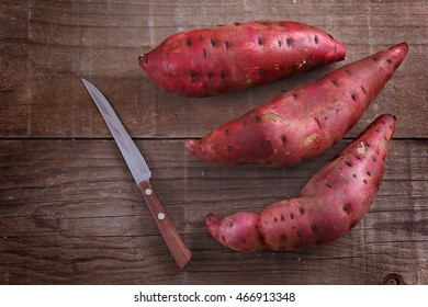 Top view of red sweet potato and knife over rustic wooden background