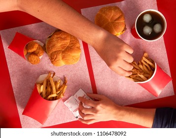 Top view of red table with hands picking on food friends sharing and stealing food