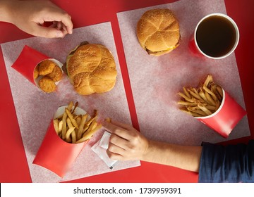 Top view of red table with wendy burgers and hands picking on food friends sharing and stealing food