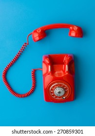 top view of red vintage phone with handset off the hook, on blue background