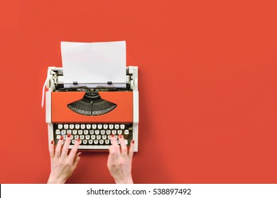 Top view of red vintage typewriter with white blank paper sheet with female hand typing