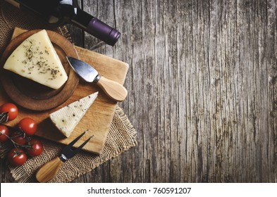 Top view of red wine and cheese on rustic wooden table background with copyspace. French cuisine product. Wine and dine still life.