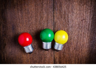 top view red,green,yellow light bulbs on wooden background.