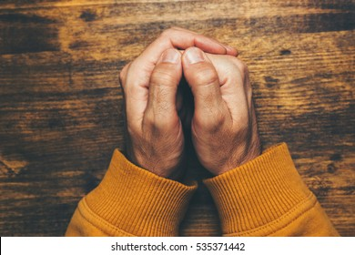 Top view of religious male crossed hands in prayer, christian religion practice