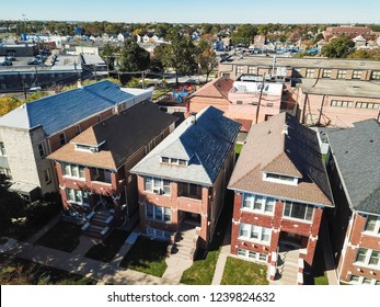 Top view residential neighborhood near business district in West of Downtown Chicago. Classical brick townhouse with green front yard lawn, colorful fall foliage