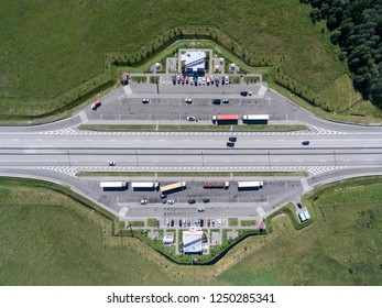 Top view at resting area of highway with parked trucks and passenger cars, cafe and toilets