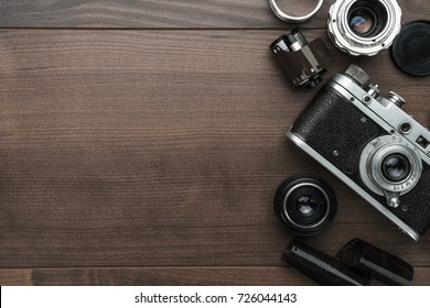 top view of retro film camera and some lenses on the wooden table with copy space