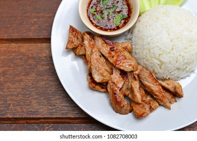 Top view of rice and fried pork with garlic and black pepper on wooden table. Serve with fresh vegetable and spicy sauce. Closeup for design-works with copy space (Thai Foods). Street foods in Bangkok
