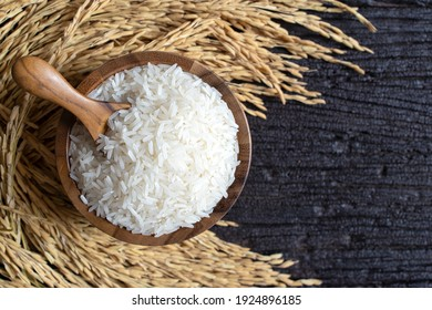 Top view of Rice (Thai Jasmine rice) with wooden spoon in wooden bowl and paddy rice on dark wooden texture background.