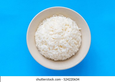 Top view rice in white bowl on blue background