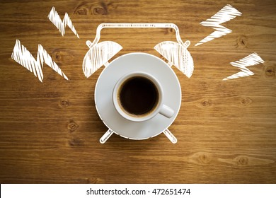 Top view of ringing coffee cup alarm clock sketch on brown wooden desktop. Time management concept