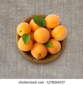 Top view. Ripe apricots on rustic background. Bowl with apricots with leaves. Ripe apricots with copy space for text. Various fresh summer fruits. Ripe and tasty apricots.